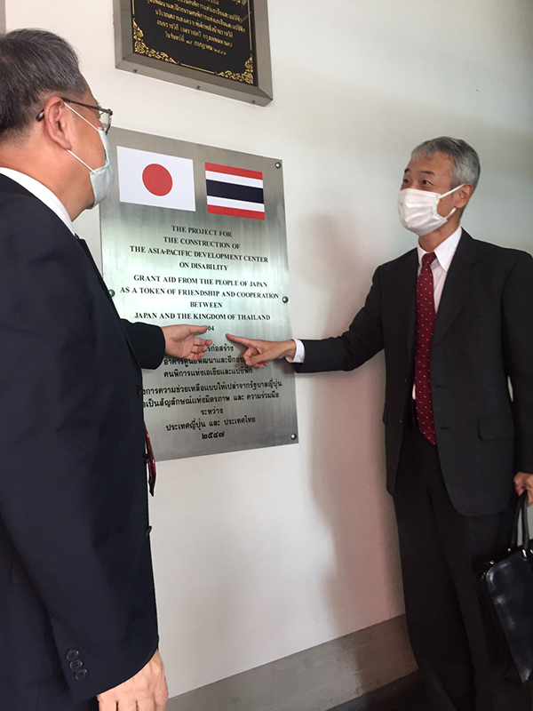 Photo of Mr. Morita and Mr. Piroon in front of a symbol of relationship between Thailand and Japan.