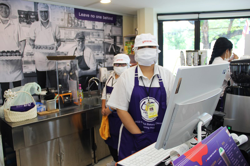 Trainees with disabilities and cafe staff wear face masks and aprons made from recycled materials.